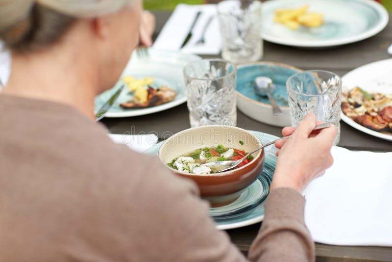 Sluit omhoog van vrouw die soep in de zomertuin eten stock afbeelding