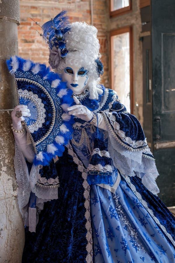 Sluit omhoog van vrouw in helder blauw en wit kostuum en overladen masker in Venetië Carnaval royalty-vrije stock fotografie