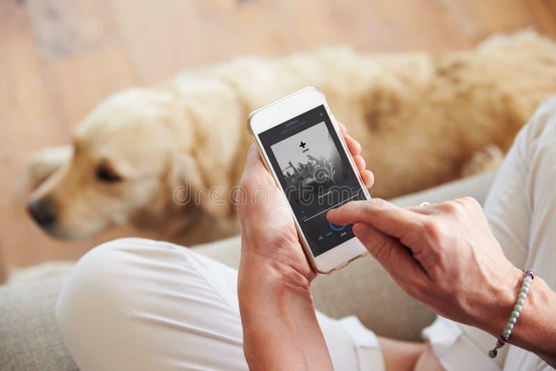 Sluit omhoog van Vrouw het Luisteren aan Muziek Smartphone thuis royalty-vrije stock foto's