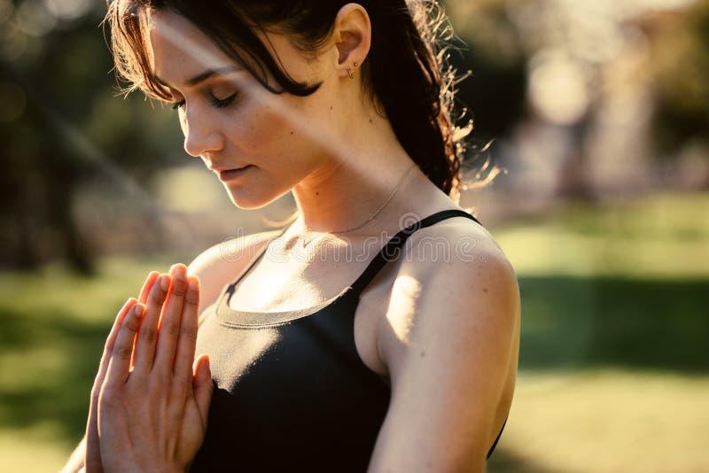 Sluit omhoog van vrouw het praktizeren aangesloten bij yoga met haar handen Geschiktheidswijfje die in openlucht bij het park in  stock foto's