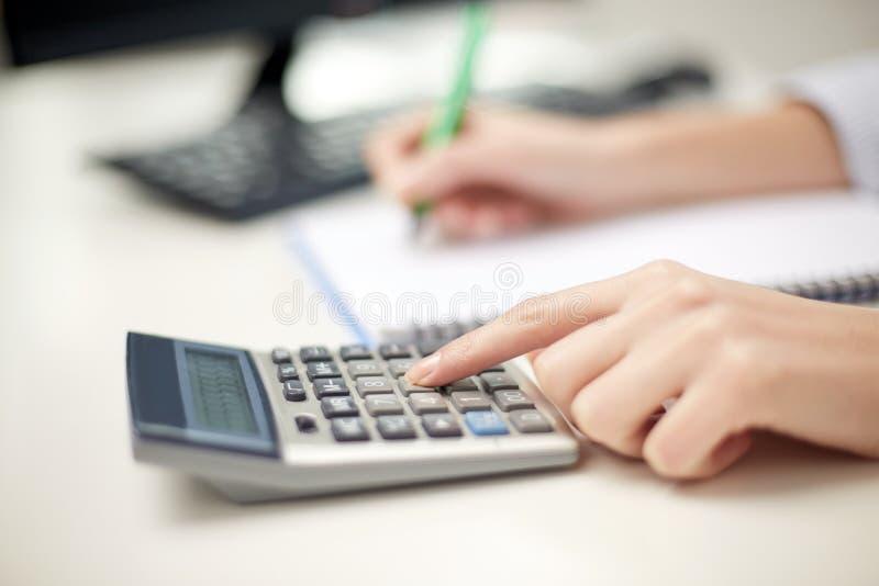 Sluit omhoog van vrouw met calculator die nota's nemen royalty-vrije stock afbeeldingen