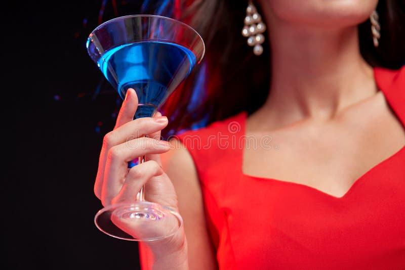 Sluit omhoog van vrouw met cocktail bij nachtclub stock afbeelding