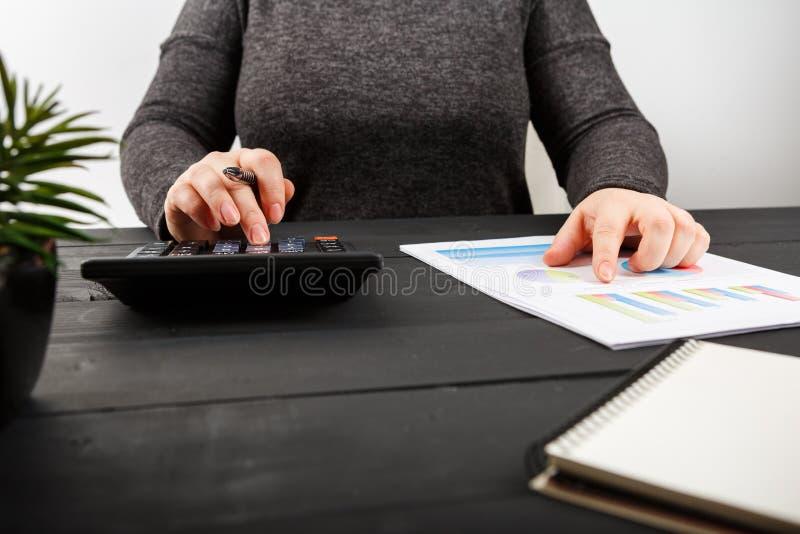 Sluit omhoog van vrouwelijke accountant of bankier die berekeningen maken royalty-vrije stock fotografie