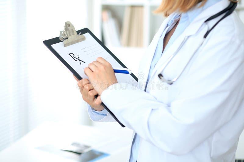 Sluit omhoog van vrouwelijke arts die een medisch voorschrift schrijven bij klembord terwijl status royalty-vrije stock afbeelding