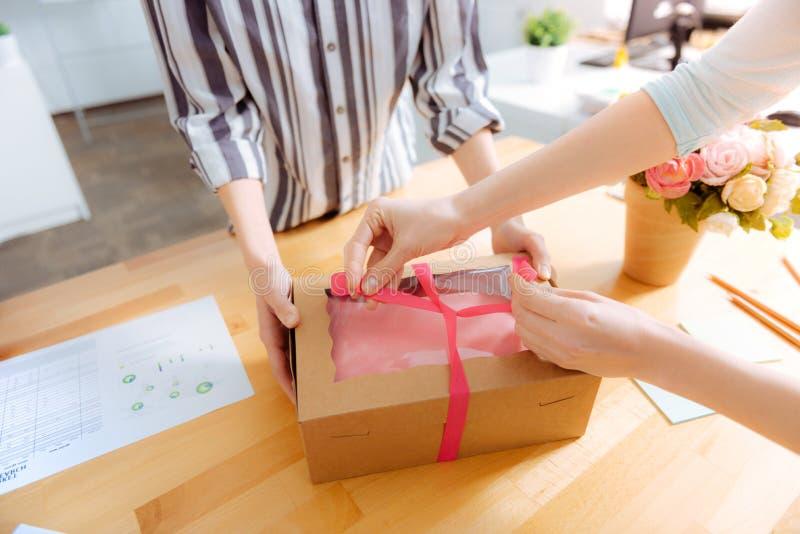 Sluit omhoog van vrouwelijke handen die bindende doos in een boog stock fotografie