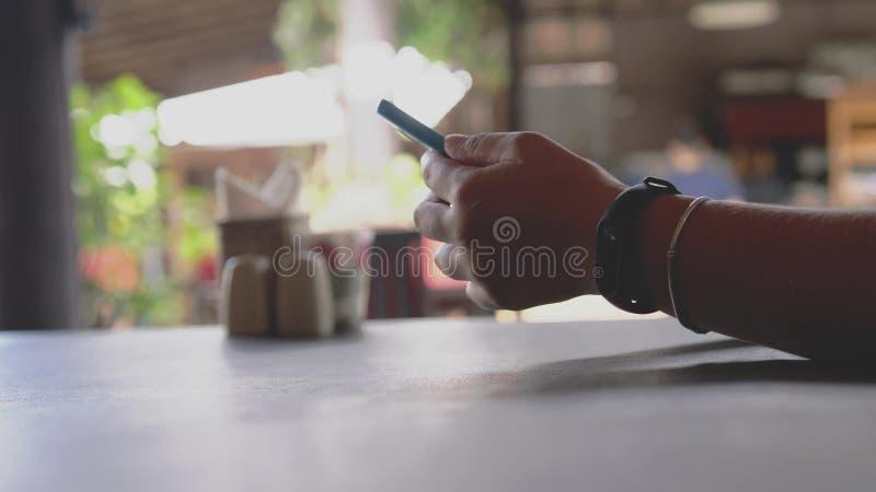 Sluit omhoog van vrouwelijke handen die klok met pedometer dragen scrollend slimme telefoon, surfend Internet, in koffie met vaag royalty-vrije stock fotografie