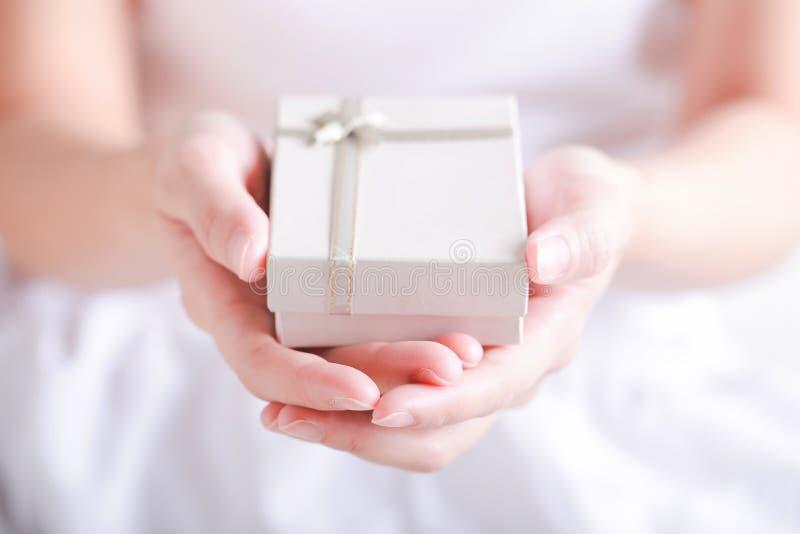 Sluit omhoog van vrouwelijke handen houdend een kleine die gift met ribbo wordt verpakt stock fotografie