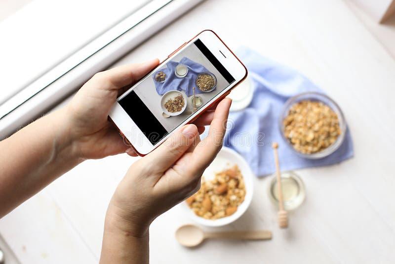 Sluit omhoog van vrouwelijke handen houdend mobiele telefoon die een beeld van granolagraangewassen, melkyoghurt en vegetarische  stock afbeeldingen