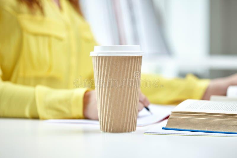Sluit omhoog van vrouwelijke handen met boeken en koffie stock fotografie