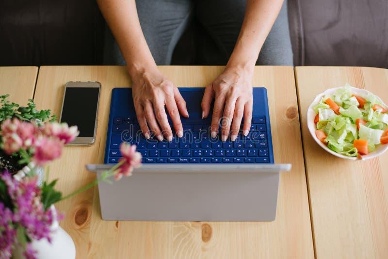 Sluit omhoog van vrouwelijke handen thuis typend op laptop toetsenbord stock afbeeldingen