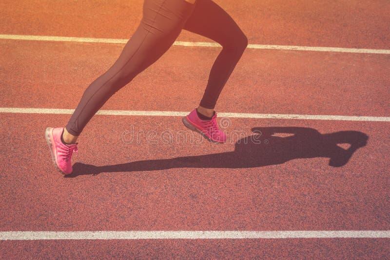 Sluit omhoog van vrouwelijke joggerbenen die op atletisch spoor lopen stock foto's