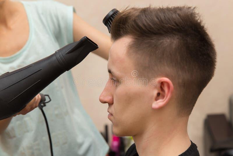 Sluit omhoog van vrouwelijke kapper die haar mannelijk klanten` s haar in haar herenkapper drogen stock foto