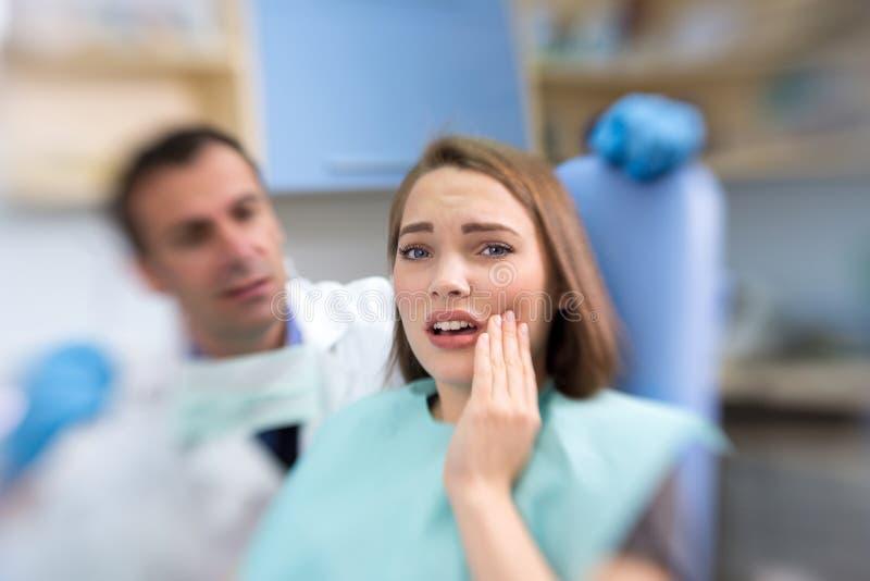 Sluit omhoog van vrouwelijke patiënt met tandpijn in tandkliniek stock afbeeldingen