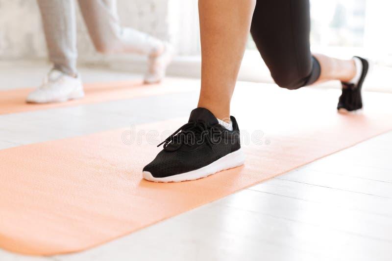Sluit omhoog van vrouwelijke voet die zijnd in moderne tennisschoenen royalty-vrije stock foto