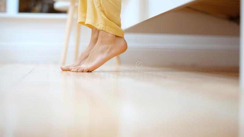Sluit omhoog van vrouwelijke voeten die van bed in de ochtend weggaan stock afbeelding