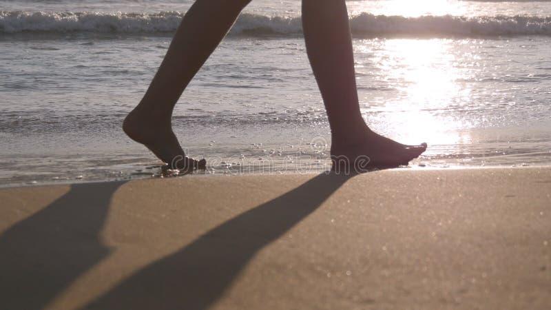 Sluit omhoog van vrouwelijke voeten lopend op gouden zand bij het strand met oceaangolven bij achtergrond Benen van het jonge vro stock fotografie