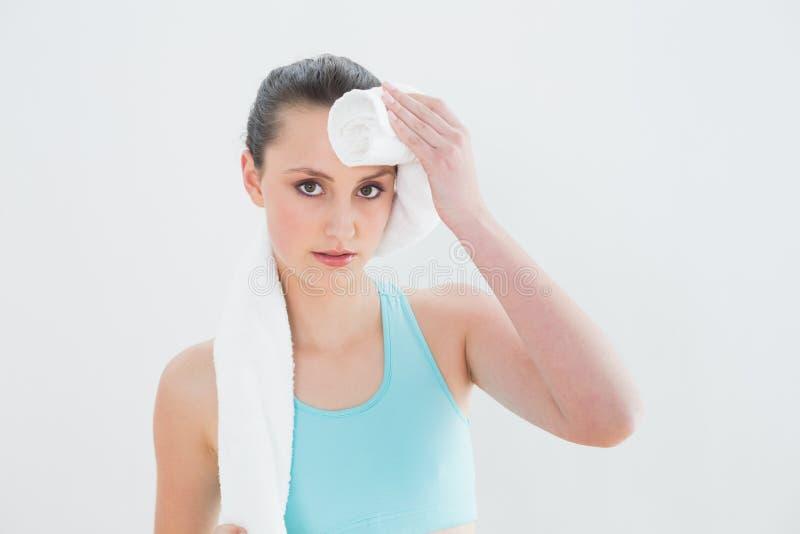 Sluit omhoog van vrouwen afvegend zweet met handdoek tegen muur stock fotografie