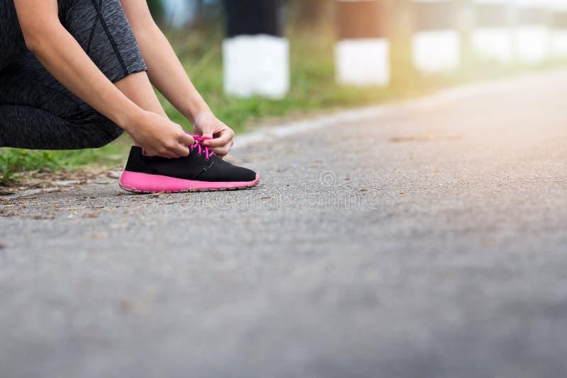 Sluit omhoog van vrouwen bindende schoenveters in openlucht royalty-vrije stock afbeelding
