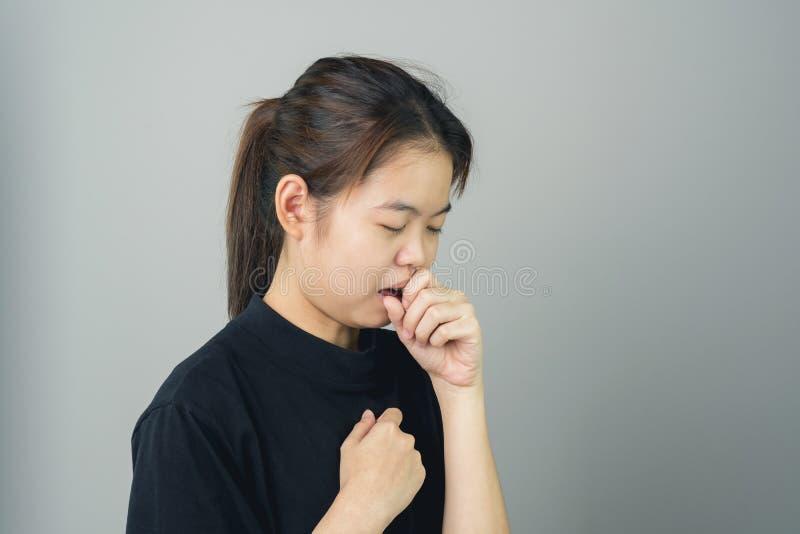 Sluit omhoog van vrouwen zijn hoest en de irritatie rond de hals, een grijze achtergrond geeft zacht licht stock afbeelding