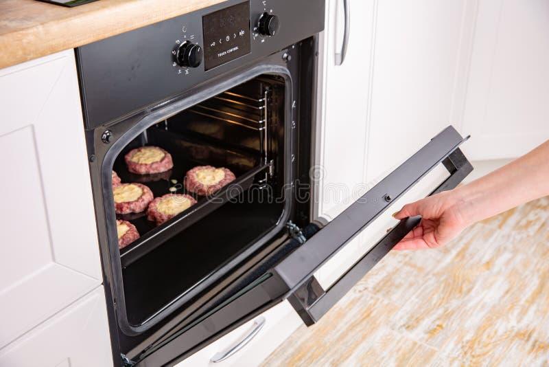 Sluit omhoog van vrouwenhand openend de ovendeur om het braadstuk te controleren royalty-vrije stock foto's