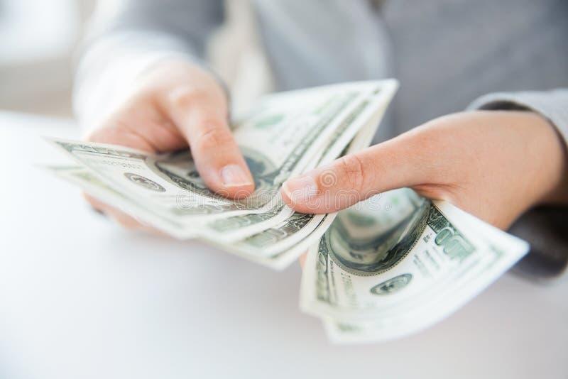 Sluit omhoog van vrouwenhanden die ons tellen dollargeld royalty-vrije stock afbeelding