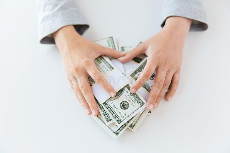 Sluit omhoog van vrouwenhanden die ons tellen dollargeld stock foto's