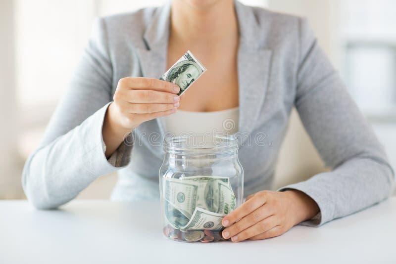 Sluit omhoog van vrouwenhanden en dollargeld in kruik royalty-vrije stock foto