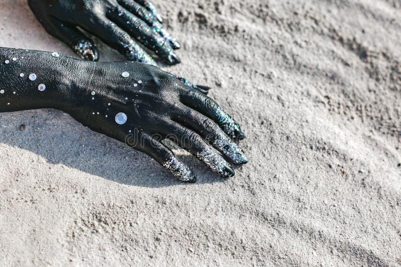 Sluit omhoog van vrouwenhanden geschilderde zwarte op zand maan en sterrenconcept royalty-vrije stock foto