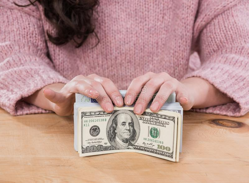 Sluit omhoog van vrouwenhanden houdend ons dollar en euro geld stock foto's