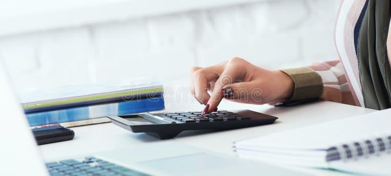 Sluit omhoog van vrouwenhanden met calculator die en nota's tellen nemen aan laptop Baan van een accountant freelancer voor stock foto's