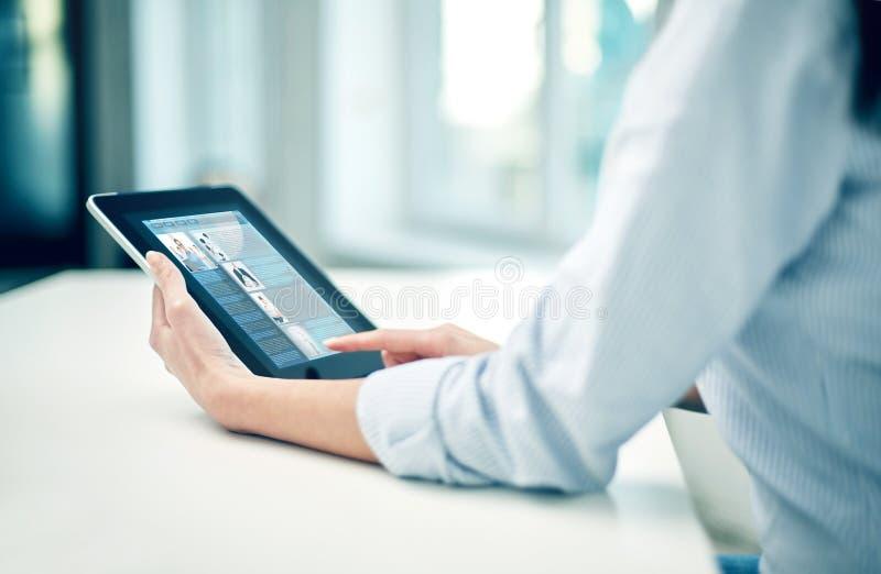 Sluit omhoog van vrouwenhanden met tabletpc op kantoor stock foto's