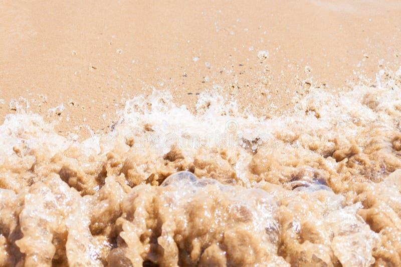 Sluit omhoog van vuile golf van overzees of oceaan op zandig strand Achtergrond stock fotografie