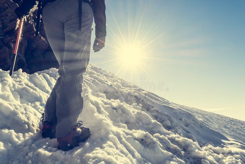 Sluit omhoog van wandelingsschoenen met ijskrappen en ijsbijl stock fotografie