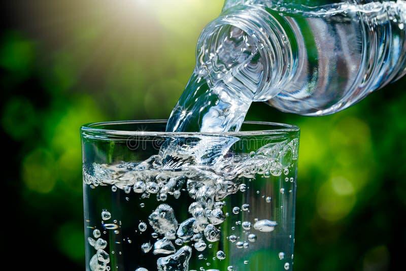 Sluit omhoog van water die van drinkwaterfles in glas op vage groene aard bokeh achtergrond stromen met zacht zonlicht stock fotografie