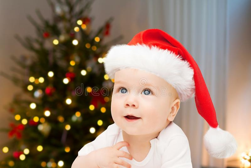 Sluit omhoog van weinig baby in santahoed bij Kerstmis royalty-vrije stock afbeelding