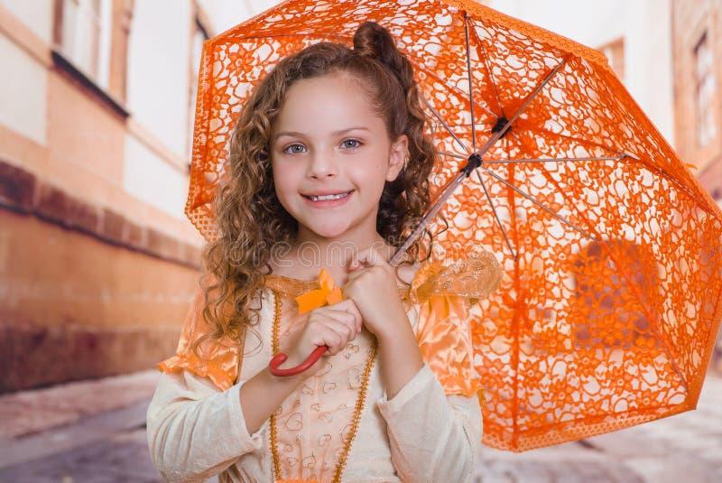 Sluit omhoog van weinig glimlachend meisje die een mooi koloniaal kostuum dragen en een oranje paraplu in vaag houden stock afbeeldingen