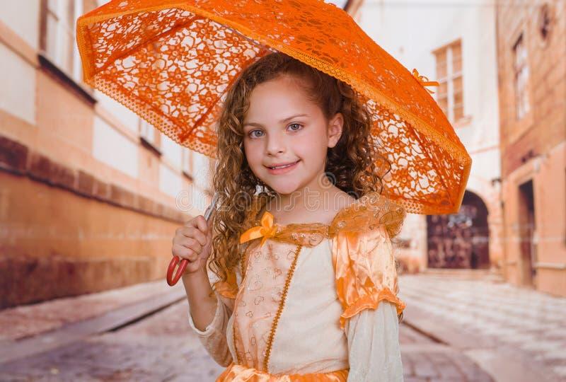 Sluit omhoog van weinig mooi meisje die een mooi koloniaal kostuum dragen en een oranje paraplu in vaag houden royalty-vrije stock afbeeldingen