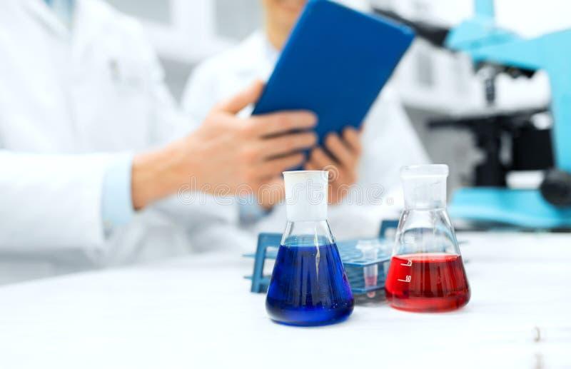 Sluit omhoog van wetenschappers met flessen en tabletpc stock afbeeldingen