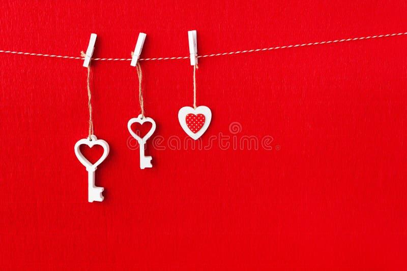 Sluit omhoog van Witte houten hartsimbol en sleutel op rode document achtergrond stock afbeeldingen