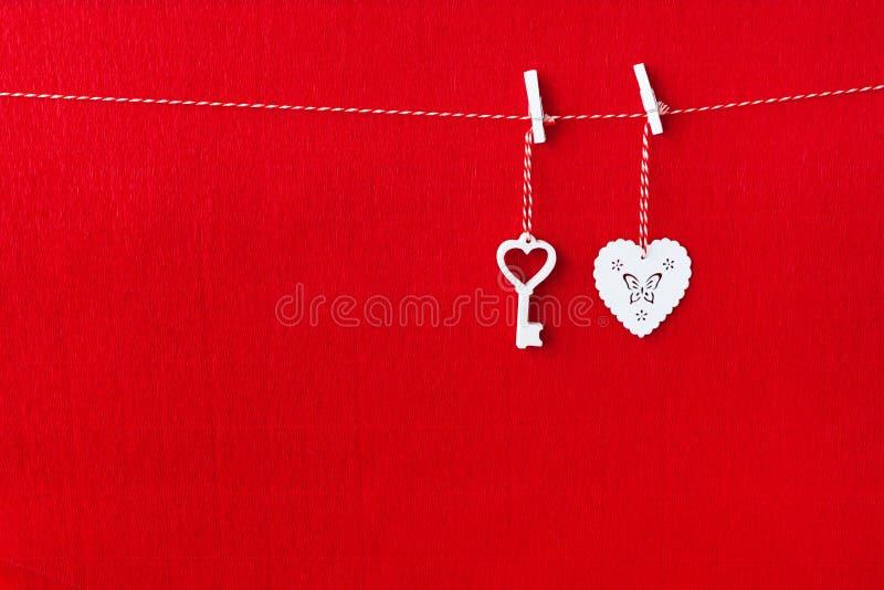 Sluit omhoog van Witte houten hartsimbol en sleutel op rode document achtergrond royalty-vrije stock afbeeldingen