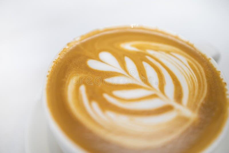 Sluit omhoog van witte kop van hete koffie latte met het hart van het melkschuim en de kunst van de bloemvorm op witte lijst royalty-vrije stock afbeeldingen