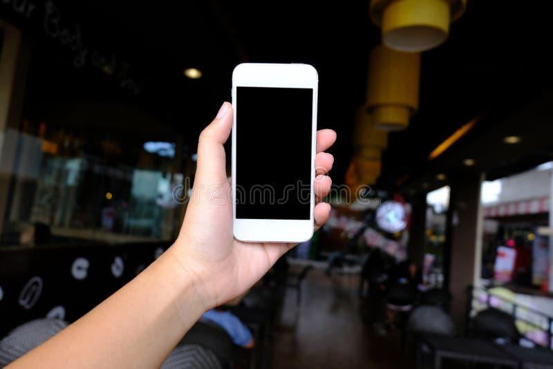 Sluit omhoog van women& x27; s handen die het lege exemplaar van de celtelefoon spac houden stock afbeelding