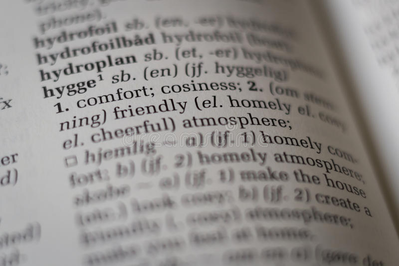 Sluit omhoog van woordenboek met het Deense die woord hygge aan het Engels wordt vertaald stock afbeelding