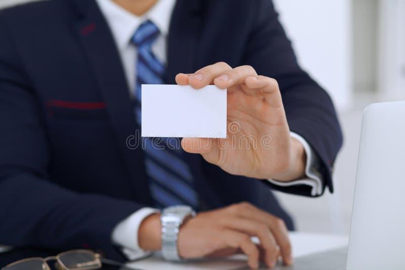 Sluit omhoog van zakenman of advocaat die een adreskaartje geven terwijl het zitten bij de lijst Hij die vennootschap aanbieden e royalty-vrije stock fotografie