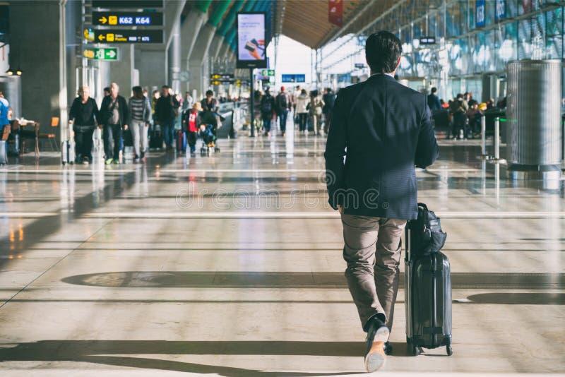 Sluit omhoog van zakenman dragende koffer terwijl het lopen door een terminal van het passagiersvertrek in luchthaven Zakenman Tr royalty-vrije stock foto