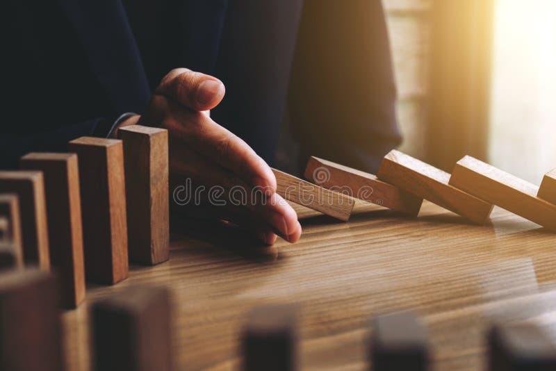 Sluit omhoog van zakenmanhand die Dalende houten Domino's EF tegenhouden royalty-vrije stock afbeeldingen
