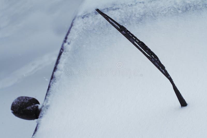 Sluit omhoog van zwarte opgeheven die autoruitewisser in sneeuw wordt behandeld stock foto