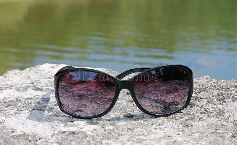 Sluit omhoog van zwarte zonnebril met purpere lenzen op rots met binnen erachter water royalty-vrije stock afbeelding