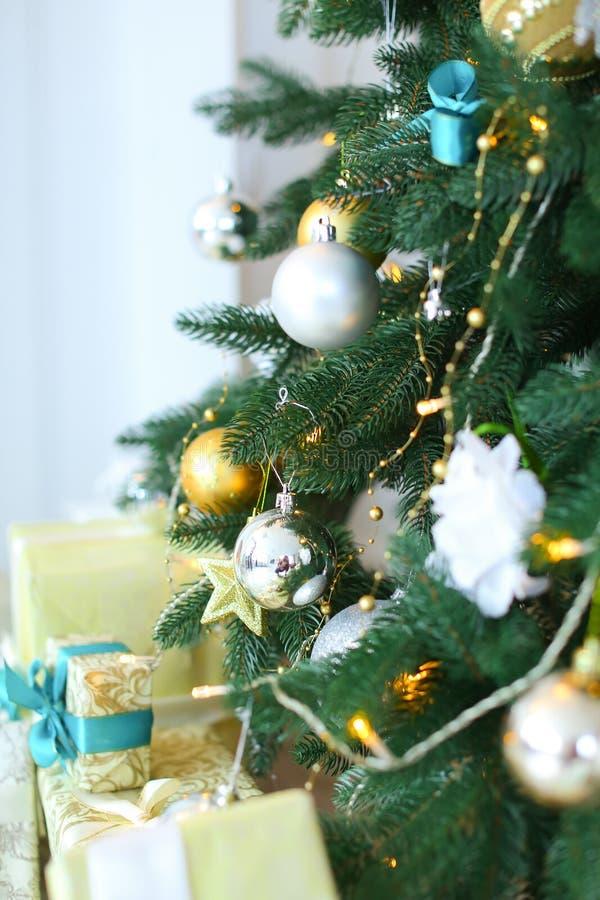 Sluit omhoog verfraaide Kerstboom met gele slingers en stelt voor royalty-vrije stock afbeelding
