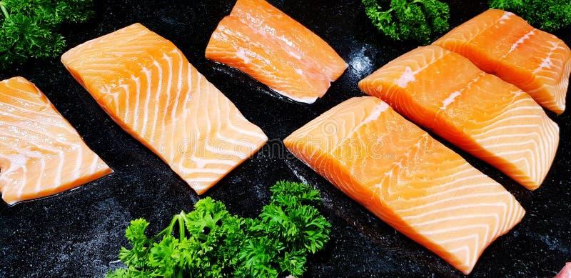 Sluit omhoog verse die Zalm en Tonijnvissen met groente op zwarte plaat bij versheidsmarkt worden gesneden royalty-vrije stock foto